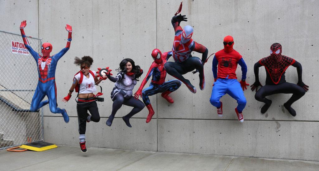 Pessoas fantasiadas como  diferentes versões do homem aranha